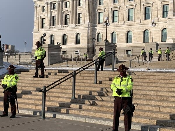 Officers stand on the steps in front of a large building.