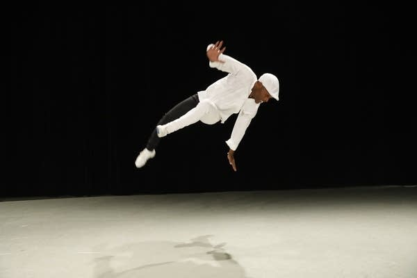 still of a man in the air, dancing on a stage