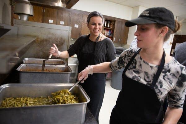 Hannah Litfin (left) and Rachel Friesen prepare hot meals.