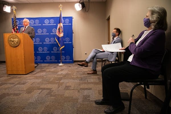 Two people wearing masks sit while a man at a podium speaks.