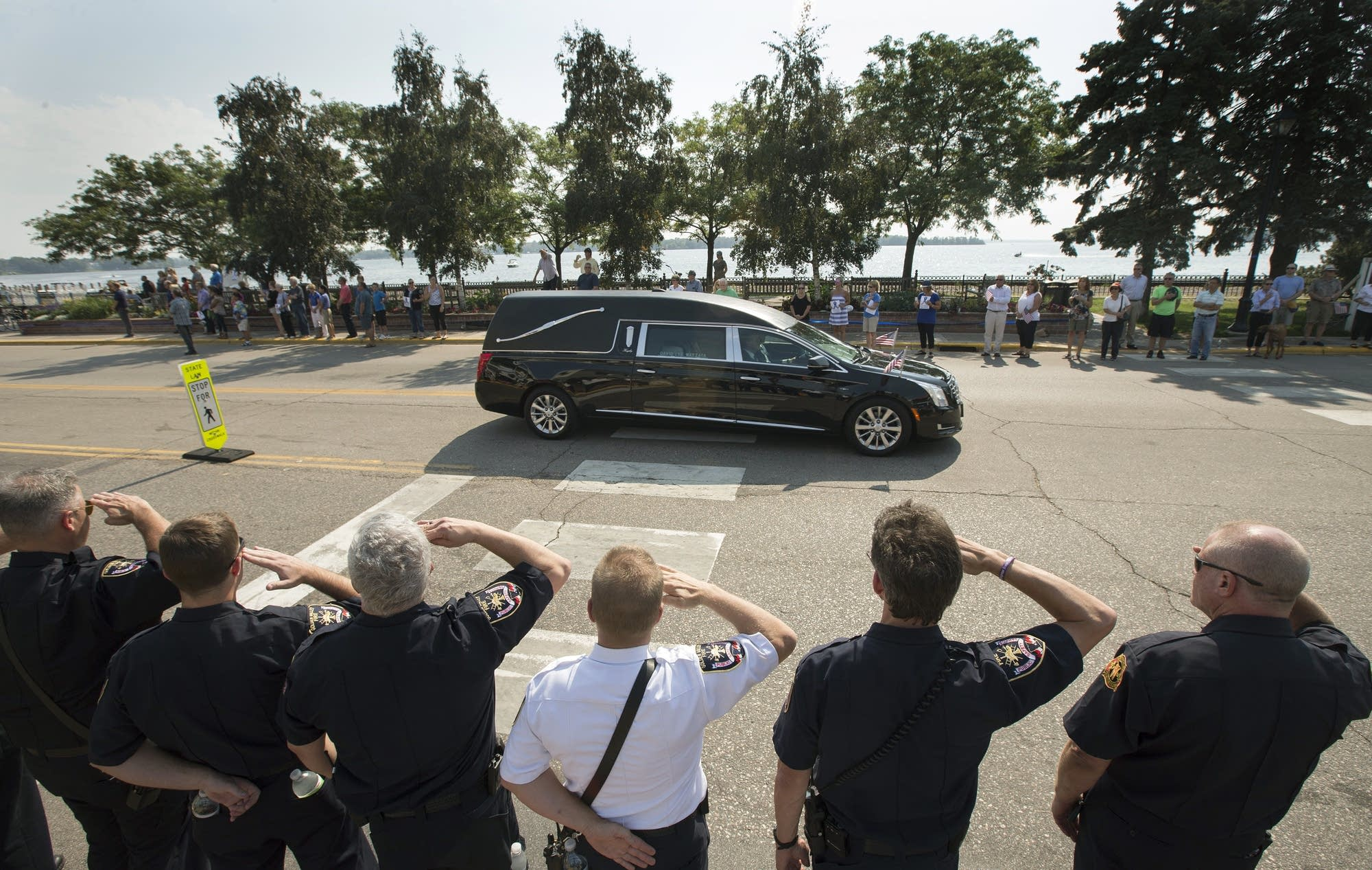 Police officers salute the funeral procession for officer Bill Mathews.