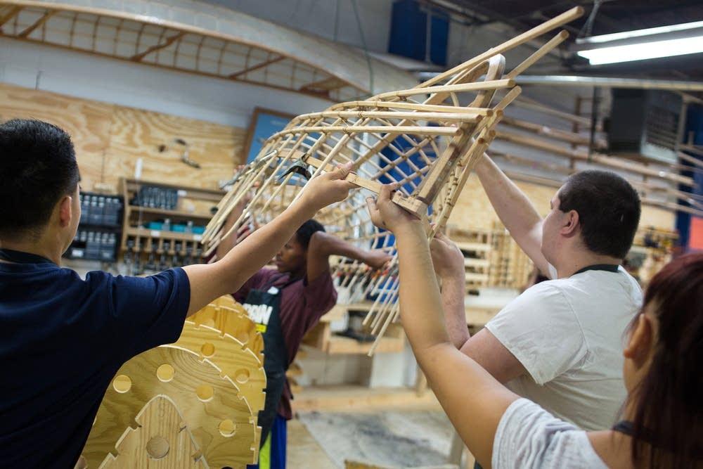 Lifting a hand-made canoe frame