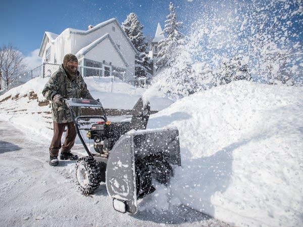 Tong Vang, 33, uses a snowblower