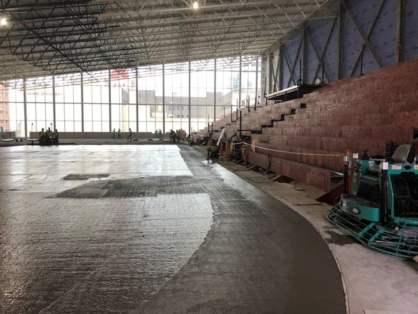 Workers pour concrete onto the Minnesota Wild's new practice rink.