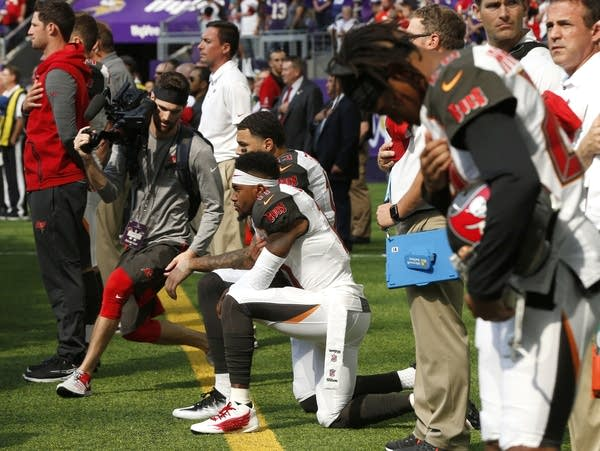 Tampa Bay Buccaneers players take a knee during anthem