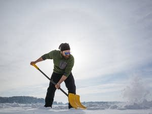 Ted Ozersky clears snow from a patch of ice he wants to measure
