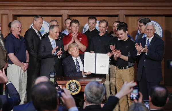 President Donald Trump holds up signed Energy Independence Executive Order