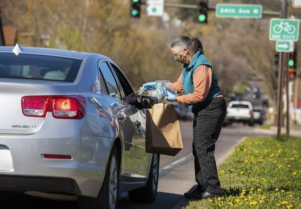 Person hands a brown bag to someone in a car.