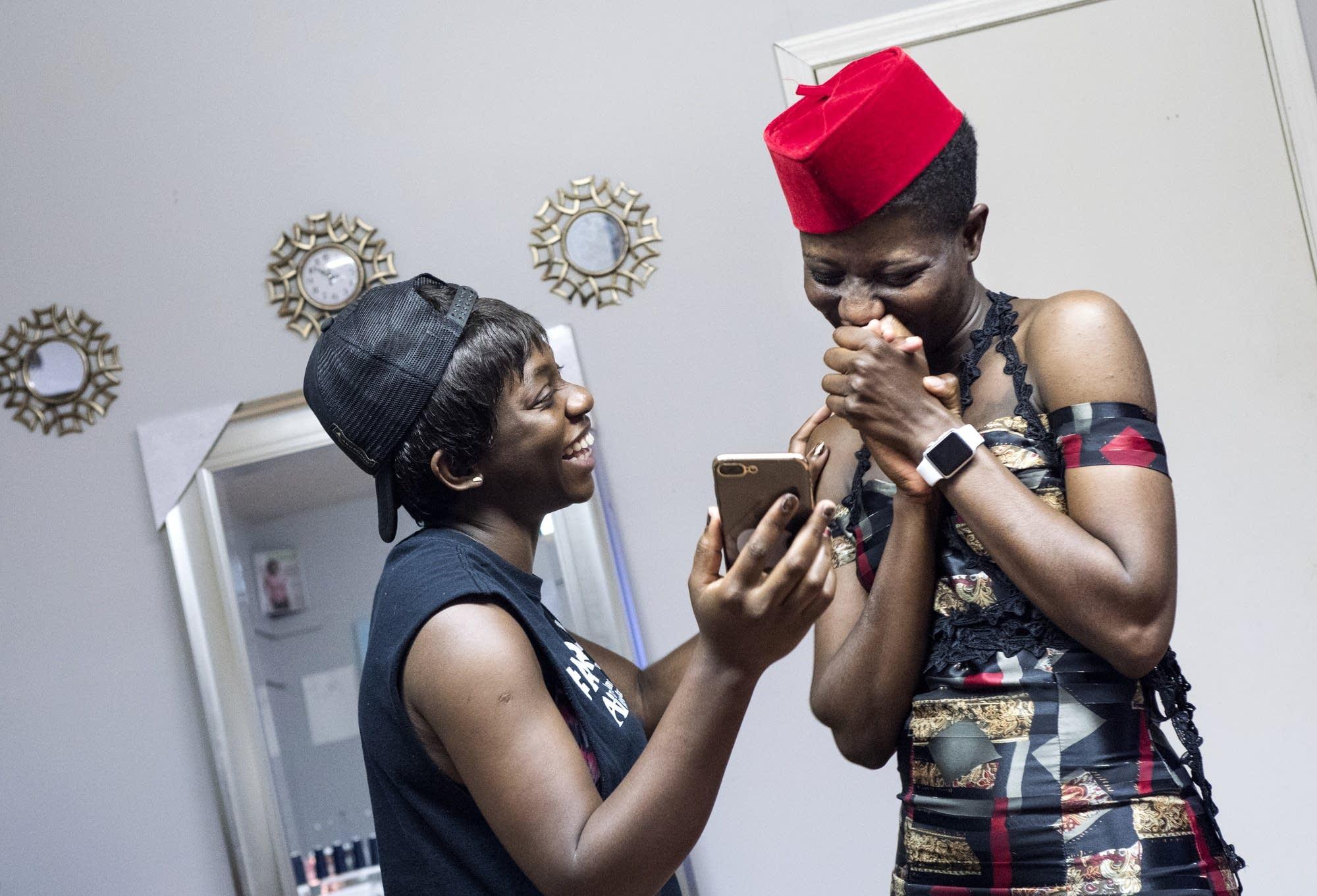 Designer Jacqueline Addison, left, shows model Setor Nyendu a video.