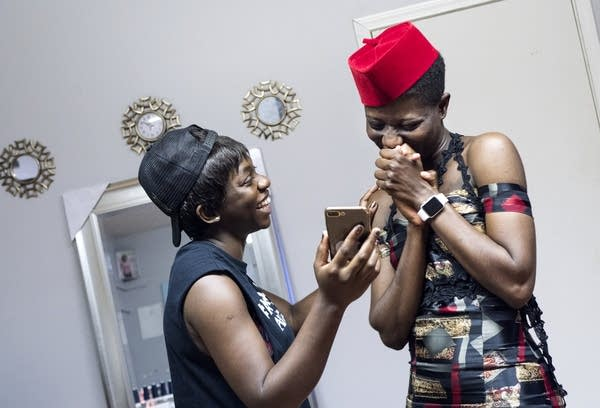 Designer Jacqueline Addison, left, shows model Setor Nyendu a video.