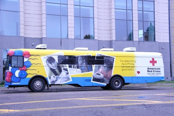 A yellow and blue bus with a Red Cross logo.