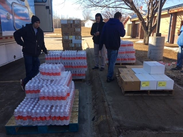 Santee Sioux Tribal Members unload bottled water and food.