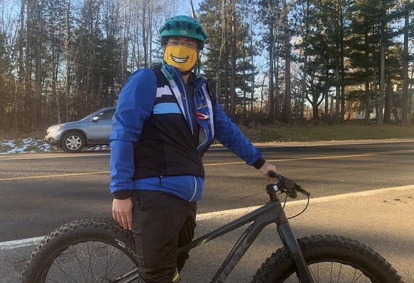 A person wearing a face mask on a bike.