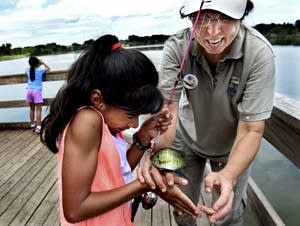 Michelle Kelly instructs Joeslyn Salgado-Ayala on how to release a fish.