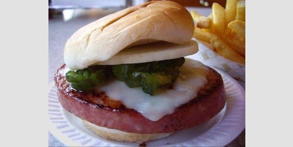 Thick-cut fried bologna sandwich on a white bun w/ pickles, cheese, onions