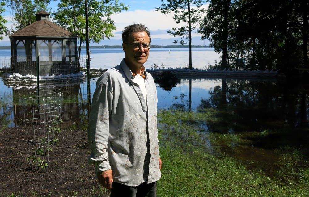 Fred Smith stands in his flooded Rainy Lake yard.