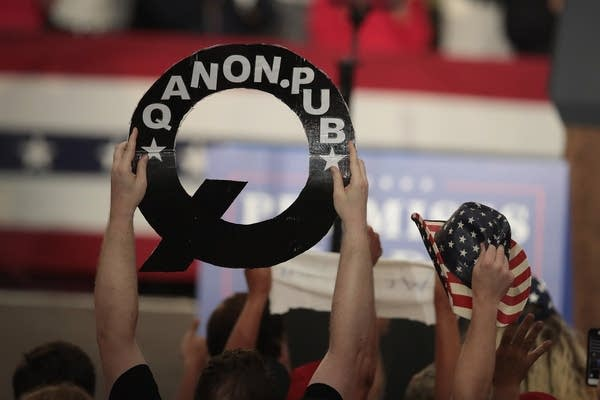"""A person holds a """"Q"""" sign standing for """"QAnon."""""""