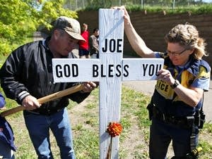 Officer Lucia Wroblewski helped Mark Schannach erect a memorial cross.