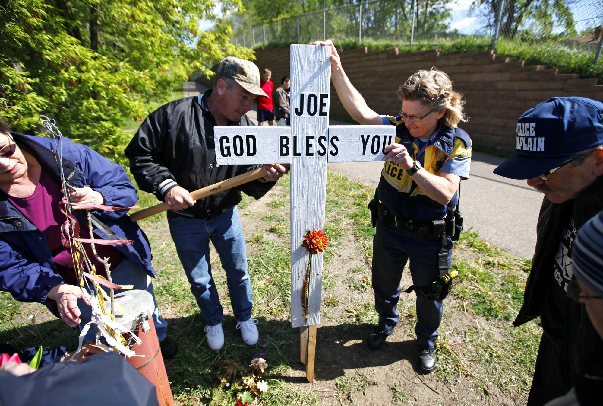 Officer Lucia Wroblewski helped Mark Schannach erect a memorial cross.