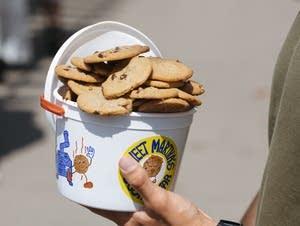 A fairgoer holds a full bucket of Sweet Martha's cookies.