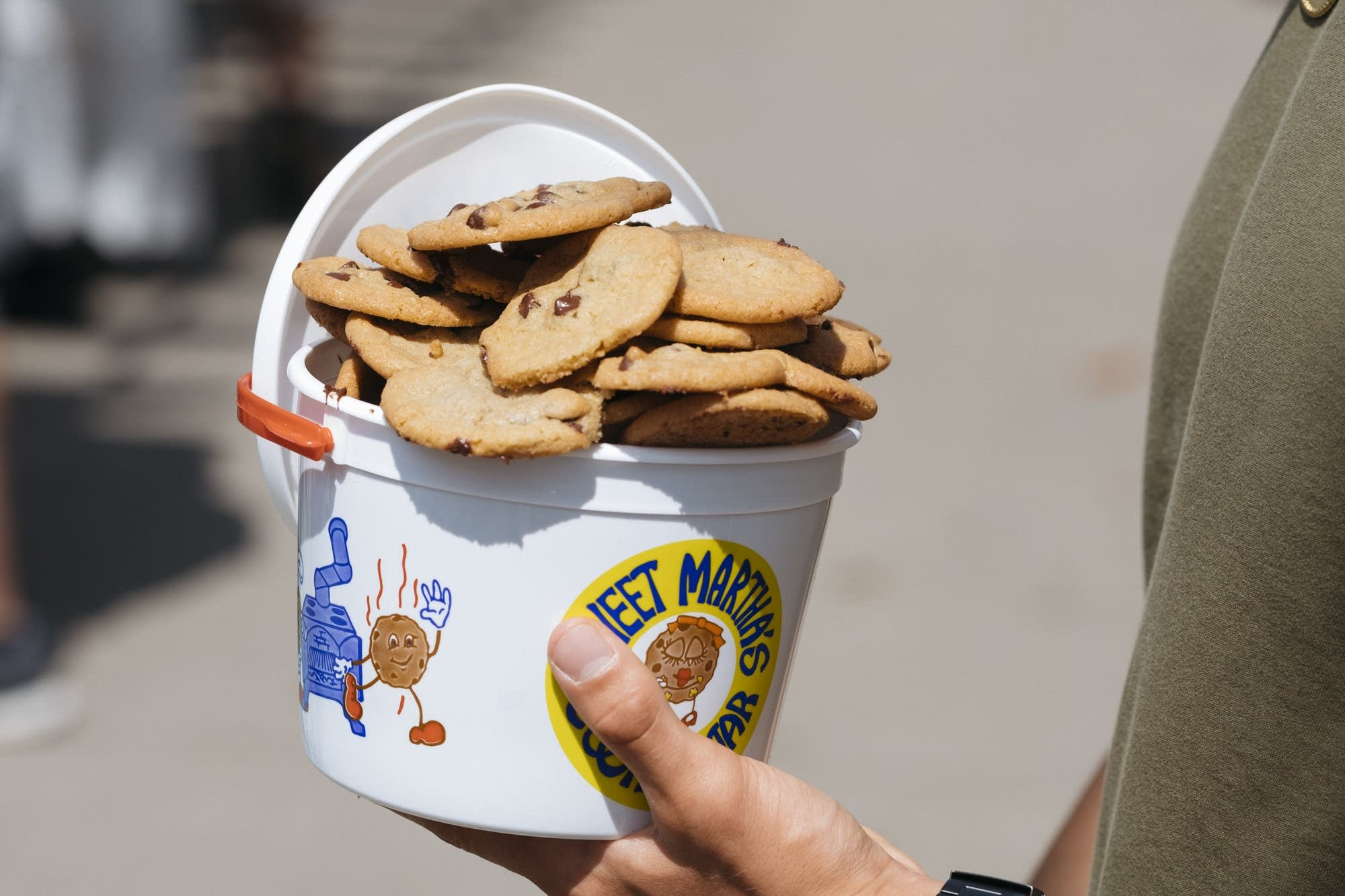 A fairgoer holds a full bucket of Sweet Martha's cookies.