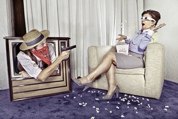 Woman wearing 3-D glasses w/ Cowboy leaning out of TV towards her