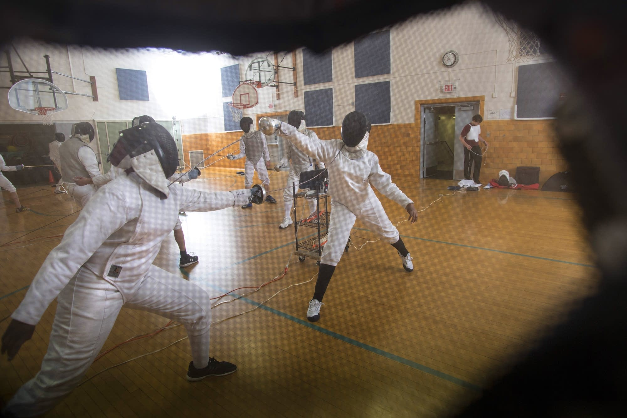 The STEM Academy girls team practices, seen through a fencer's mask.