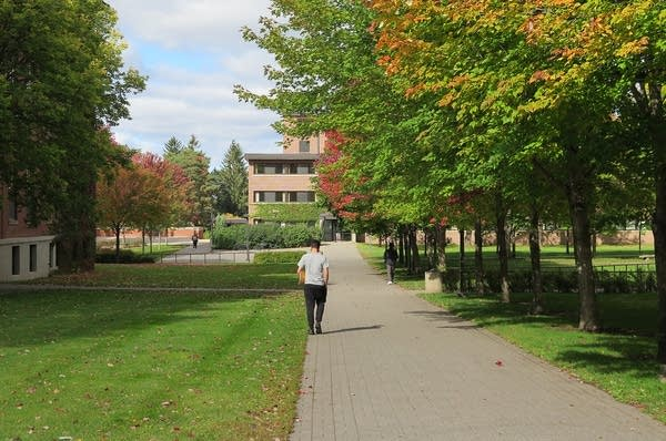 A person walking outside on campus.