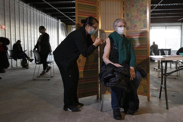 A woman sits in a chair as she receives a vaccine.