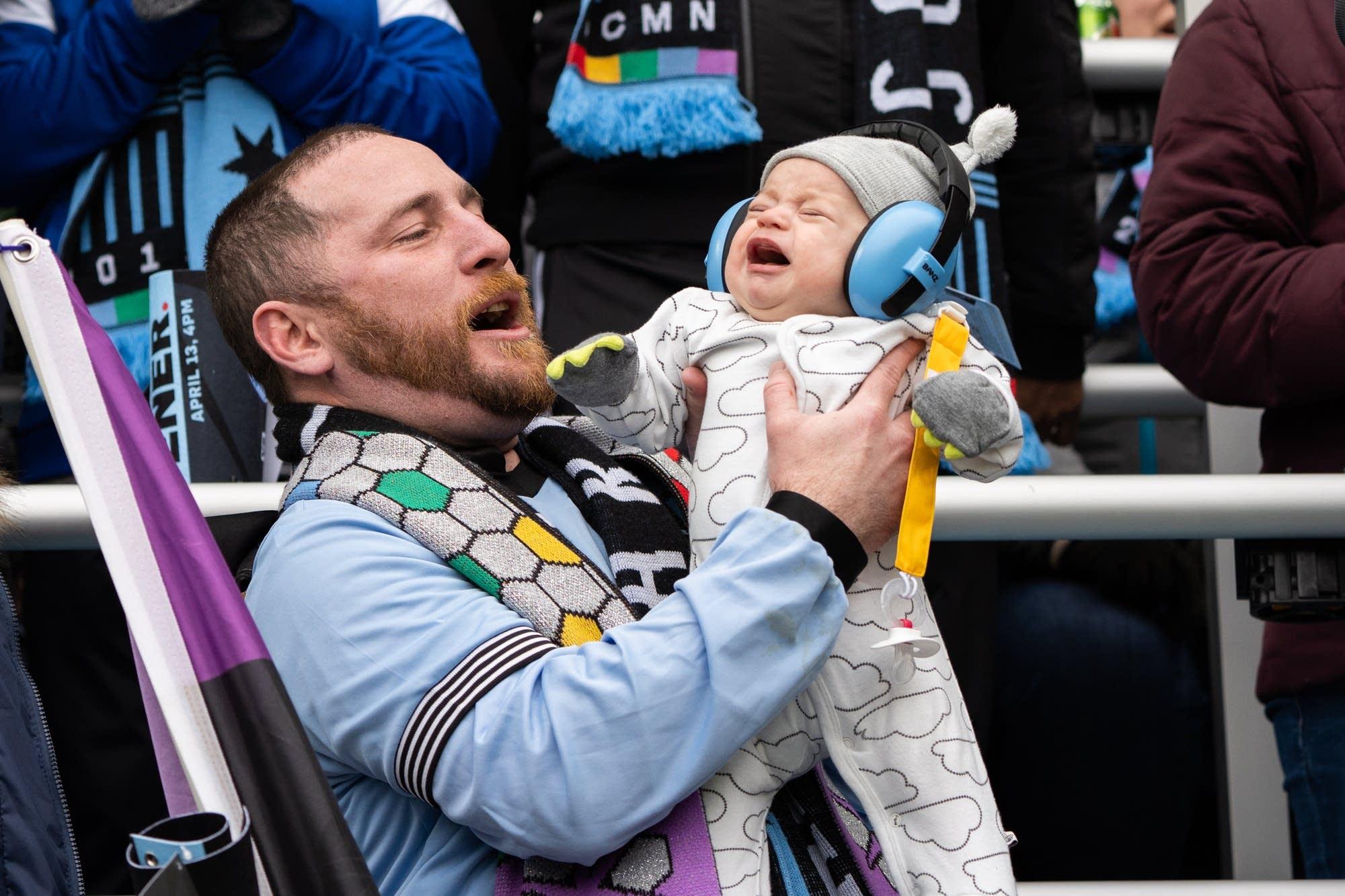 David Zeller holds 3-month-old Ragnar while cheering for Minnesota United.