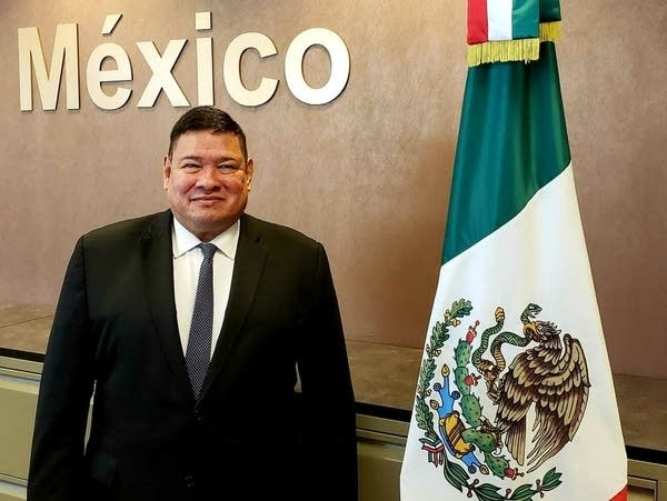 a man stands next to a Mexican flag inside of a building