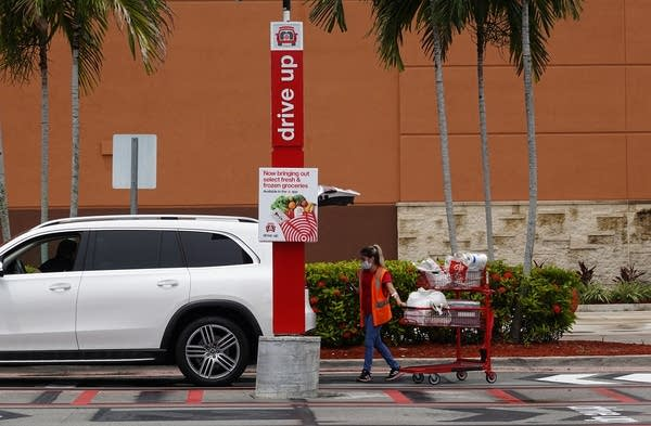 A person with a cart walks up to a car.