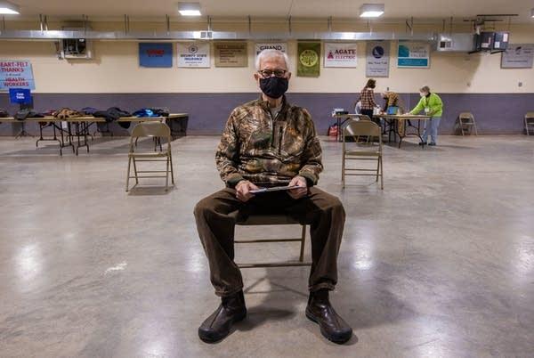 A man sits in a chair waiting.