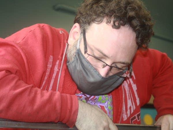 a man wearing a mask leans forward