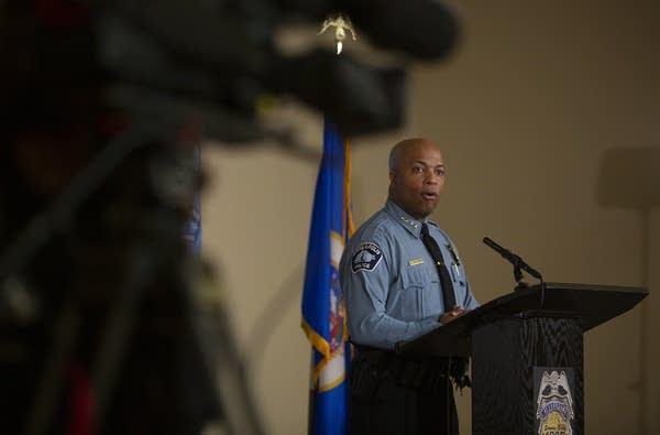 Person wearing a law enforcement uniform speaks at a podium.