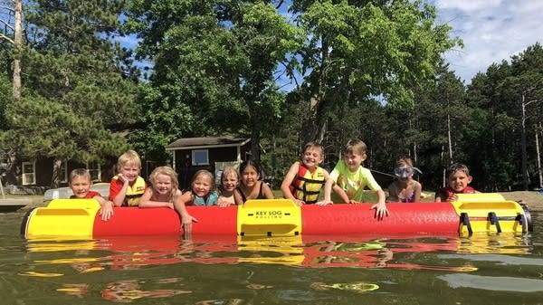 Campers encourage each other to learn to log roll at Northern Pines Camp.