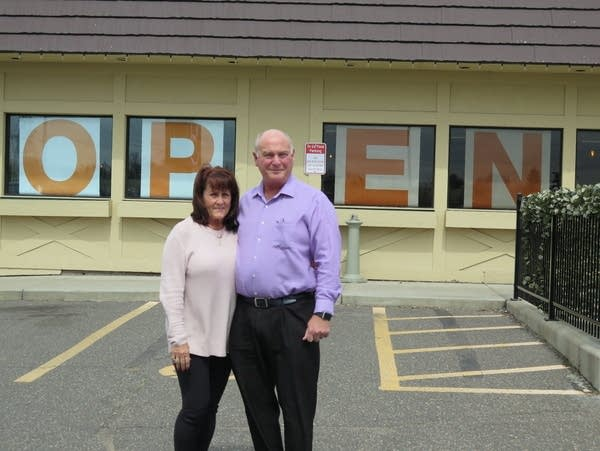 """A couple stand in front of a building with """"OPEN"""" signs in the windows"""