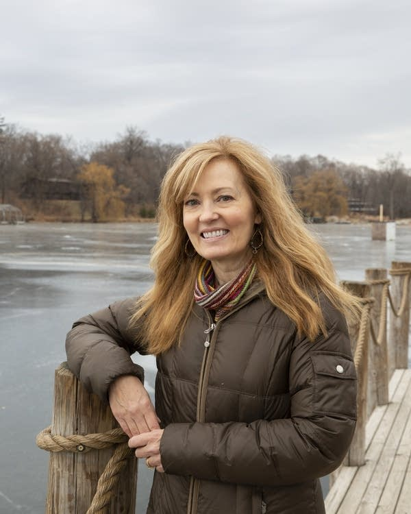 A woman standing on a dock at a lake.