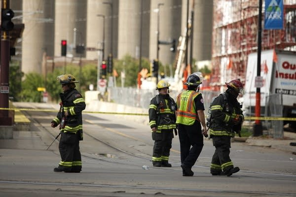 Firefighters stand by after police evacuate the area due to a gas leak.