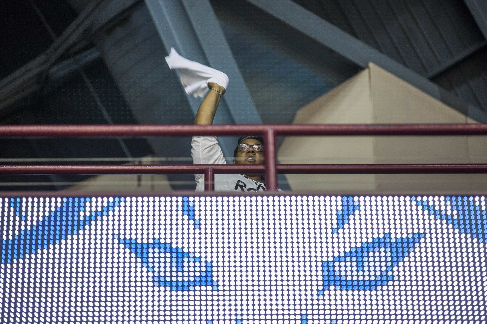 A Minnesota Lynx fan waves a towel in in the upper deck of Williams Arena.