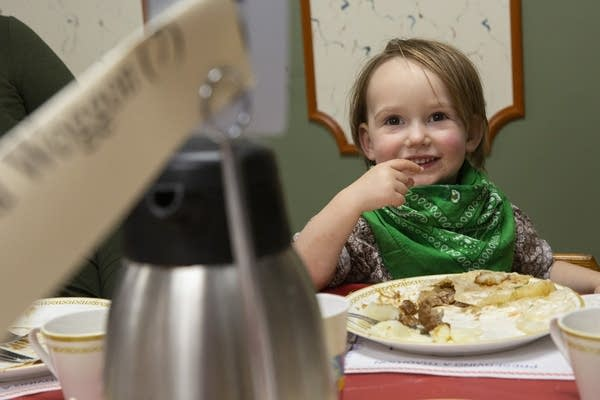 A boy wearing a green bandana around his neck smiles at the table.