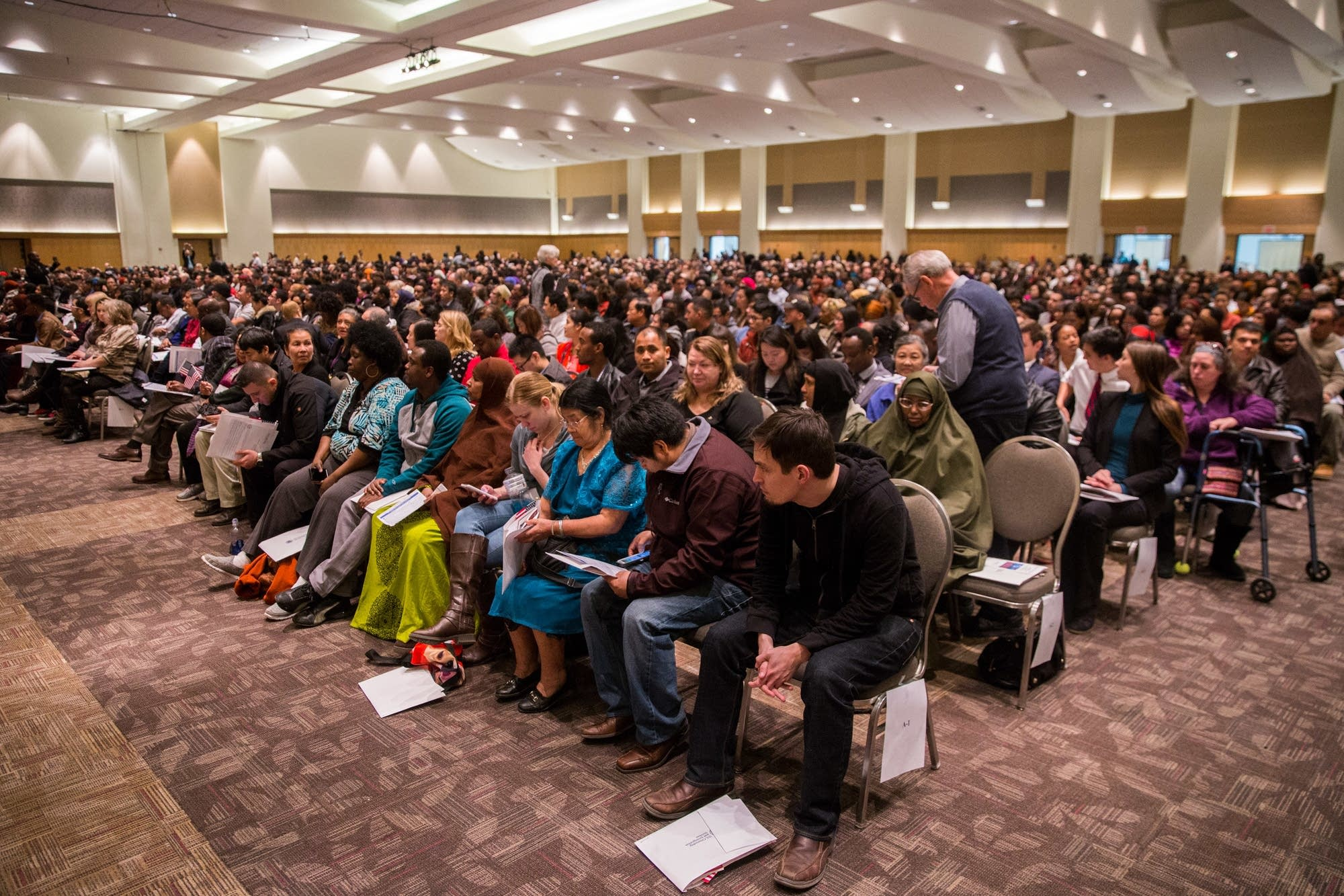 878 soon-to-be U.S. citizens wait to be naturalized.