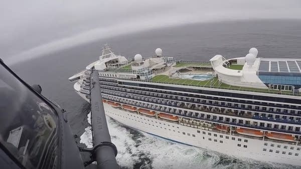 A helicopter flies over the Grand Princess ship
