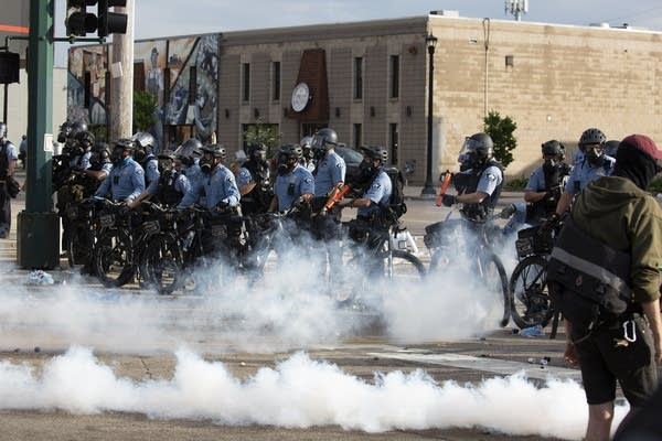 A line of police officers on bicycles in riot gear
