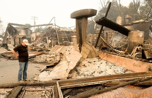 Rene Byck looks over remains of his Paradise Ridge Winery.