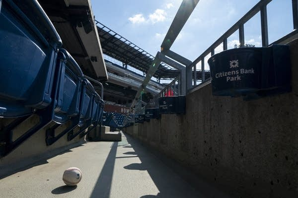 A ball that was hit into the stands sits on the floor of an empty stadium.