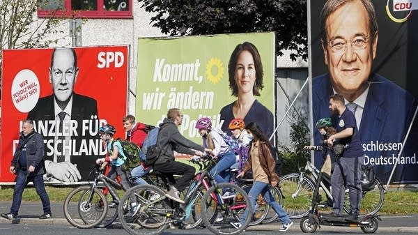 People walk and ride past election posters
