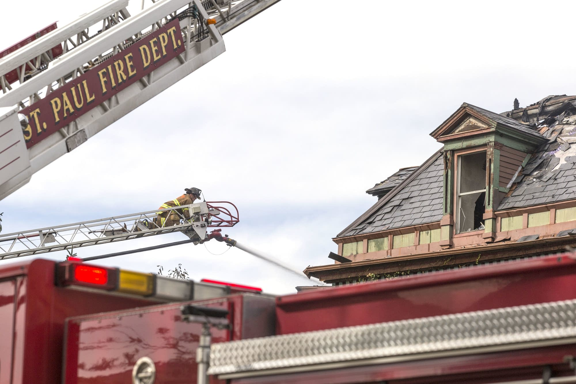 A St. Paul firefighter points an aerial stream a housefire on Tuesday.