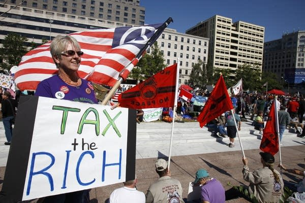 woman holds 'tax the rich' sign'
