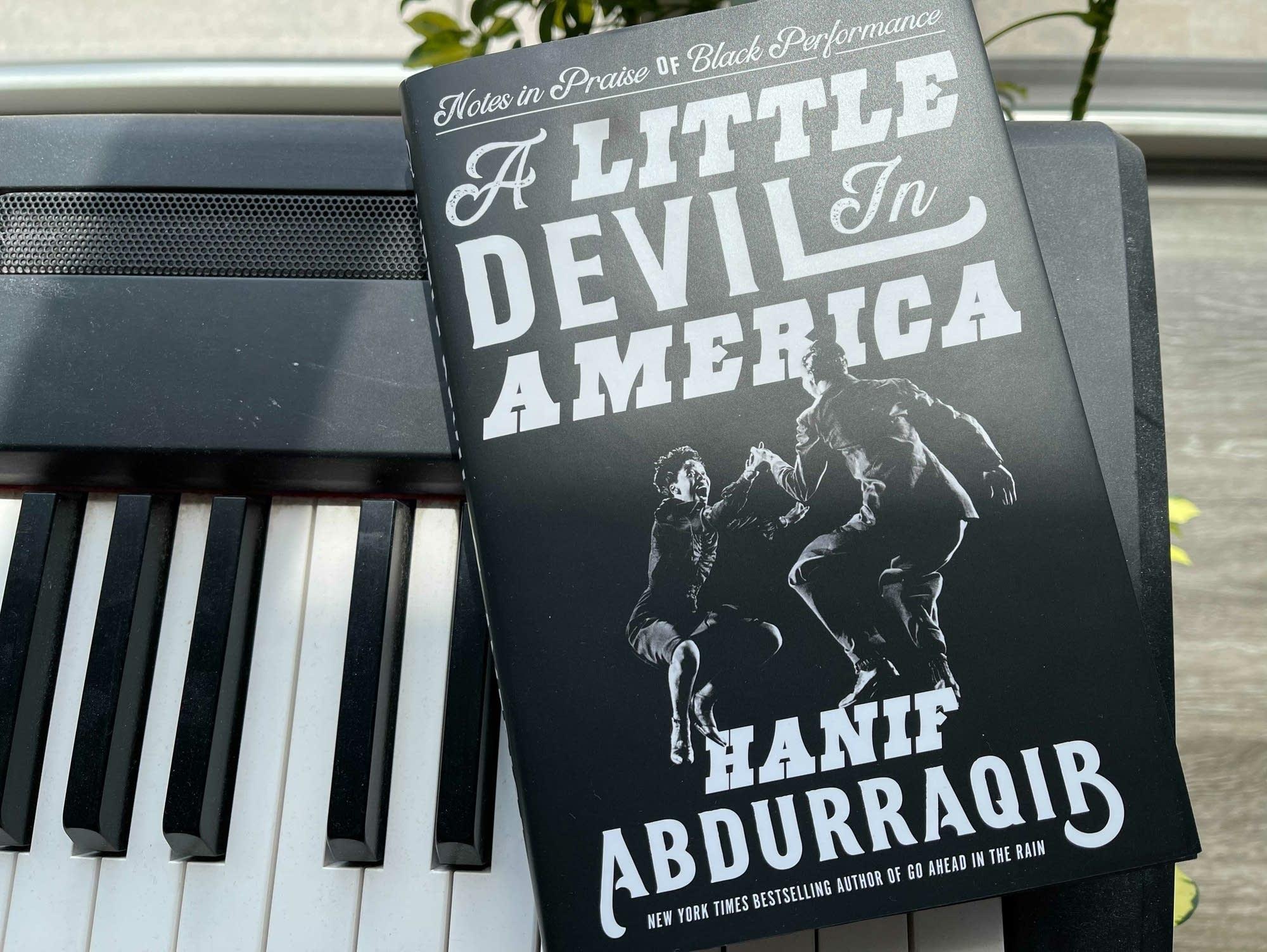 Hanif Abdurraqib book 'A Little Devil in America' on keyboard.